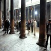 Tourists between the huge red sandstone pillars in the Church of the Nativity